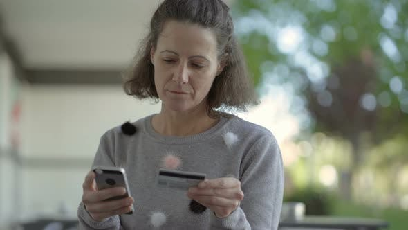 Thumbnail for Concentrated Middle Aged Woman Holding Phone and Credit Card