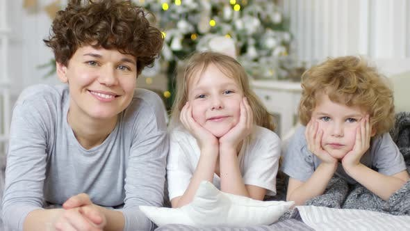 Thumbnail for Happy Family Lying on Bed and Smiling at Camera on Christmas