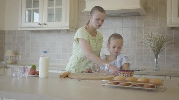 Cover Image for Mother Helping and Teaching Her Little Cute Daughter in Modern Cozy Kitchen To Cook Cake or Pancakes