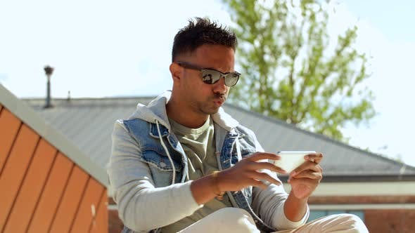 Thumbnail for Man Playing Game on Smartphone on Roof Top