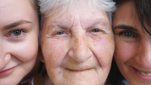 Thumbnail for Portrait of Elderly Woman with Her Daughter and Granddaughter Looking Into Camera and Smiling
