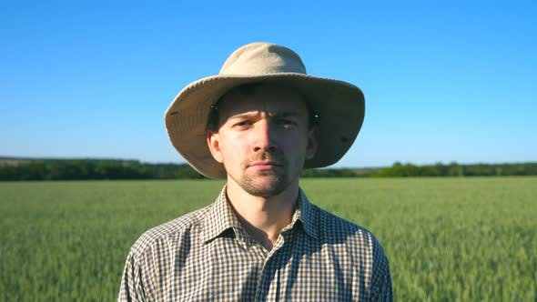 Thumbnail for Portrait of Young Handsome Farmer Looking Into the Camera and Shows Different Emotions in the Green
