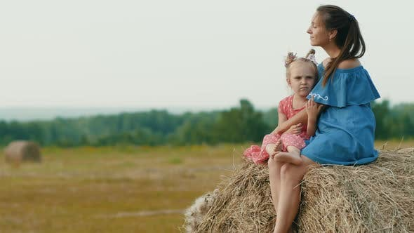Thumbnail for Mother with daughter sitting on a haystack.