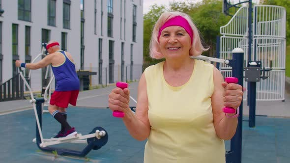 Senior Woman Grandmother Doing Active Training Weightlifting Exercising with Dumbbell on Playground