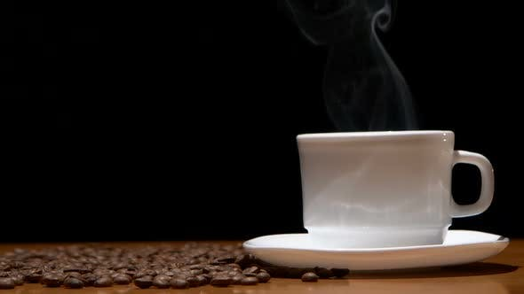 Thumbnail for White, Hot Coffee Cup and Beans on Wooden Table, Black Background.