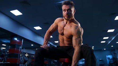 Hübscher starker junger Bodybuilder trainiert mit Hanteln. Starke Bauchmus