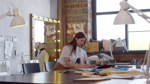 Young Woman Drawing Sketch in Sewing Studio