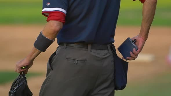 Thumbnail for The umpire at a baseball game with his score notepad.