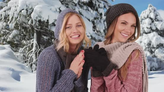 Thumbnail for Cute caucasian girls warming up with beanies and scarves on in snowy setting