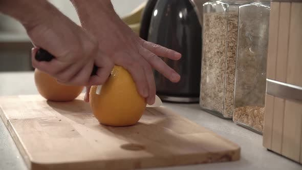 Food Preparation. Man Cutting Orange With Knife Closeup