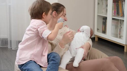 Older Boy Shaking Rattle Toy and Helping Mother Comforting and Calming Crying Baby Brother