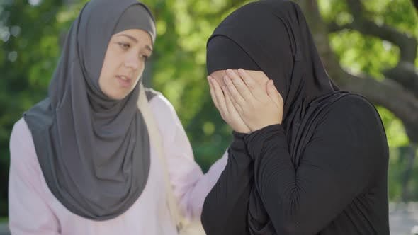 Thumbnail for Desperate Muslim Woman in Hijab Crying As Friend Calming Her Down. Portrait of Young University