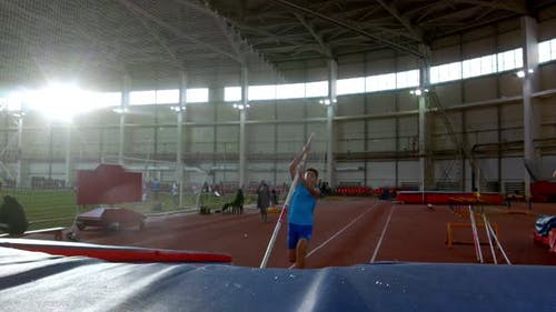 Pole Vaulting - Young Sportsman in Blue t Shirt Is Running and Jumping Over the Bar