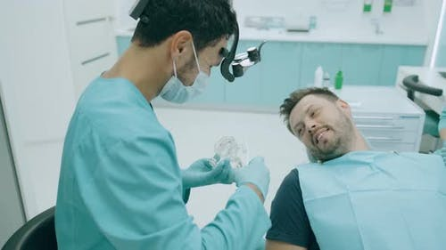 Doctor Dentist Is Showing To Happy Patient on a Jaw Model How To Clean the Teeth with Toothbrush
