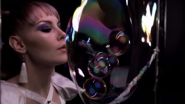 Thumbnail for Close-up: Pretty Girl Does Tricks with Soap Bubbles. She Blows a Lot of Small Bubbles