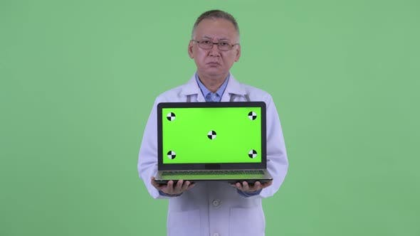 Thumbnail for Stressed Mature Japanese Man Doctor Showing Laptop