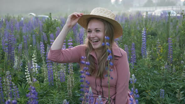 Thumbnail for Girl in Pink Dress Rises From Grass in Blooming Lupine Field and Waving Boater with Straw Hat at