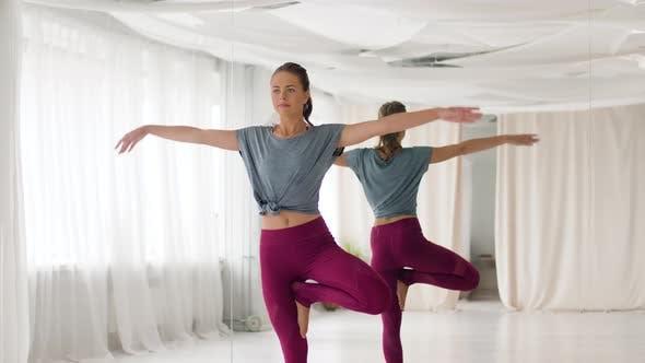 Young Woman Doing Yoga Tree Pose at Studio