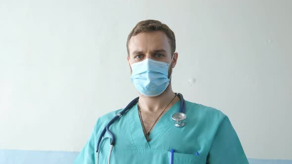 Thumbnail for Portrait of Young Male Caucasian Doctor with Medical Face Mask Looks at Camera. Medical Worker