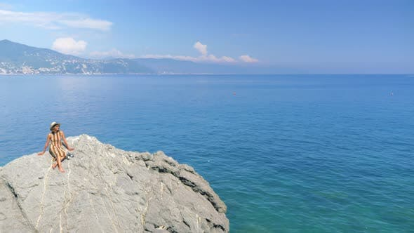 Thumbnail for A woman on rocks with a cruise ship traveling in a luxury resort town in Italy, Europe