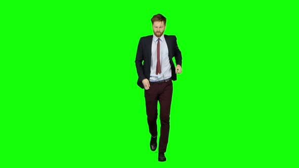 Thumbnail for Man Is Running a Telephone Rings To Him and He Talks. Green Screen