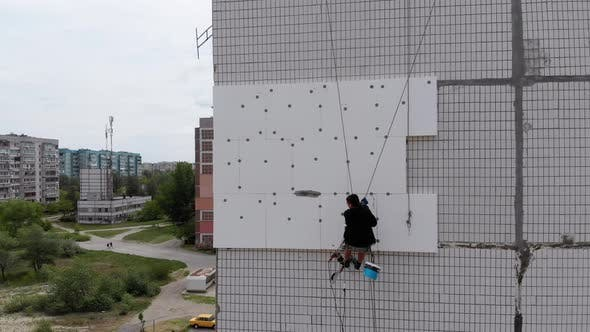 Aerial View on Industrial Climber Suspended on Ropes Performs Work on Insulation of Facade of High