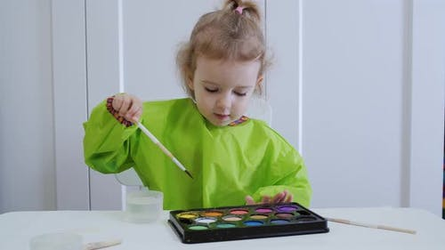 Little Toddler Child Drawing with Watercolor Paint.