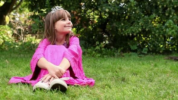 Thumbnail for Girl wearing pink dress and tiara sitting on grass
