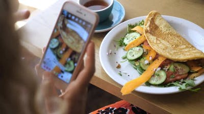 Hands Taking Picture of Healthy Organic Vegan Breakfast with Smartphone. Vegan Omelette with