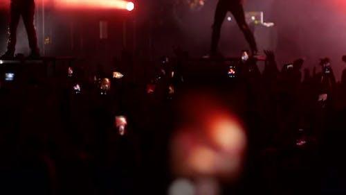 Energetische Menschen tanzen mit ihren Händen auf dem Punkkonzert - Bright Lights