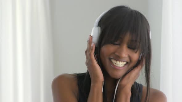 Thumbnail for Black woman listening to earphones and smiling