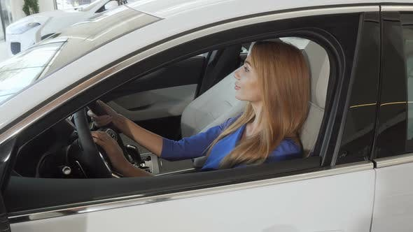 Thumbnail for Beautiful Female Driver Smiling To the Camera Sitting in a New Car at the Dealership