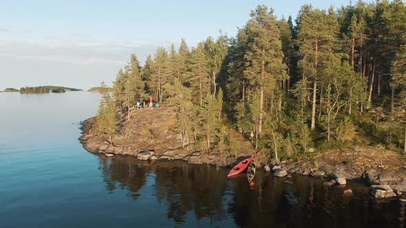 Kayaks By Rocky Bank and People Near Tent Camp on Island