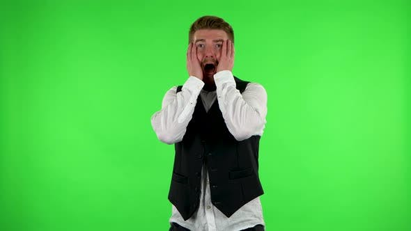 Thumbnail for Man Carefully Examines Something Then Fearfully Covers His Face with His Hands. Green Screen