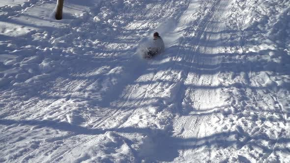 The girl rides a snow slide on sledges. Slow motion.