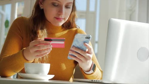 Beautiful Sunny Day Young Woman Drinks Morning Coffee in a Cafe, Making Online a Purchase Easy