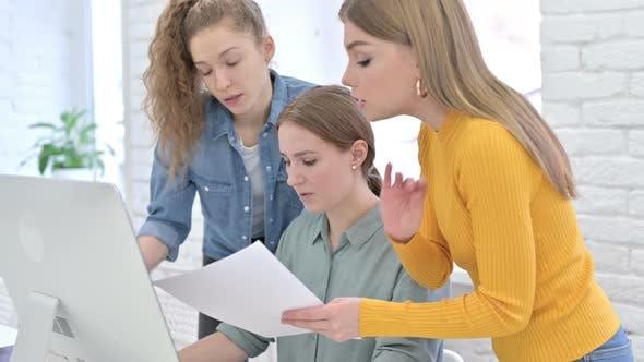 Upset Creative Startup Team Reading Documents and Using Desktop