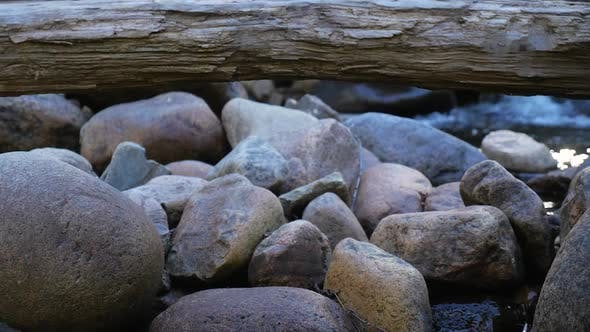 Cover Image for Rocks With Log On Top And Small Rapids Behind