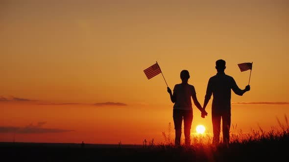 Cover Image for A Young Couple with the Flags of the United States in Their Hands Admires the Beautiful Sunset