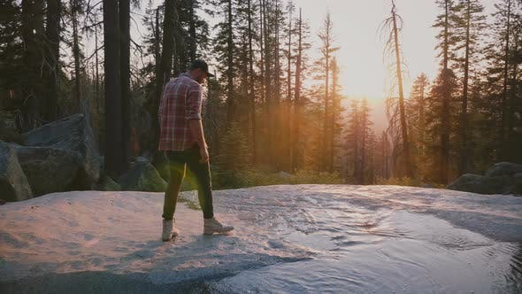 Thumbnail for Back View of Free Young Man Stepping Into Small Water Stream Enjoying Amazing Sunset Hike