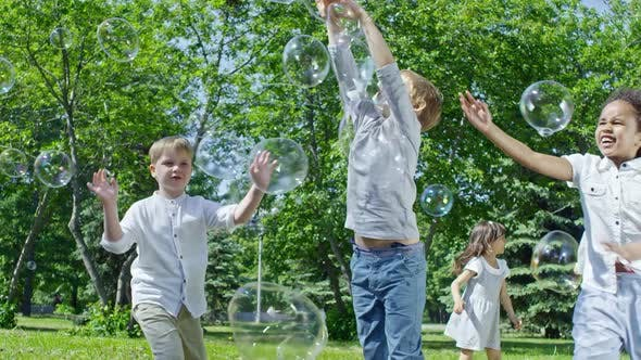 Thumbnail for Cheerful Kids Chasing Soap Bubbles