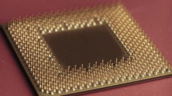 The Old Computer Processor CPU with Gold Plated Contacts Spins on Red Background