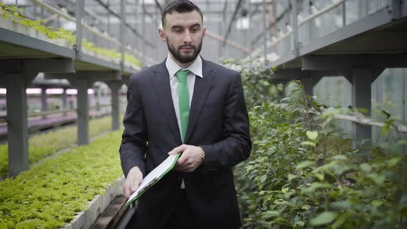 Thumbnail for Young Confident Caucasian Man in Suit Walking To Camera in Greenhouse and Leaving. Professional
