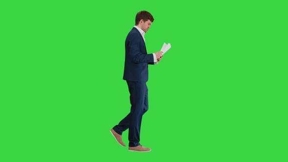Thumbnail for Concentrated Businessman Reading Documents or Report While Walking on a Green Screen, Chroma Key.