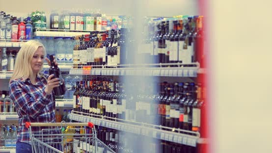 Woman Chooses Wine in the Supermarket
