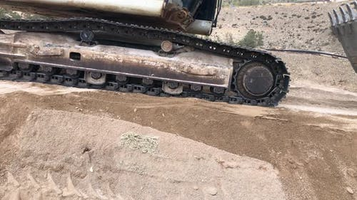 Excavator Drives By on Earth Embankment