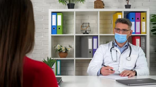 Doctor in protective medical mask, diagnoses patient, write symptoms in notebook
