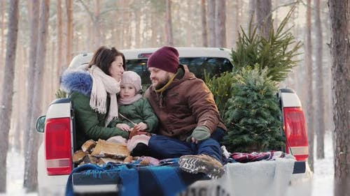 A Happy Young Family Getting Ready for the Christmas Morning, Sitting in the Back of the Car