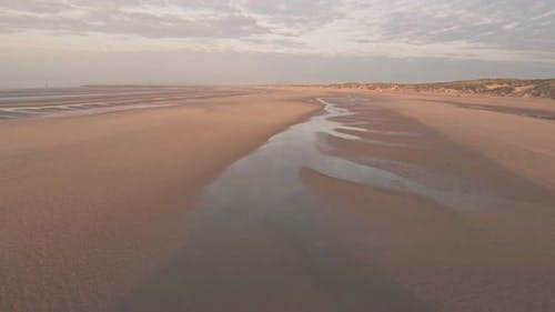Camber Sands Beach at sunset in East Sussex, England. Aerial drone view
