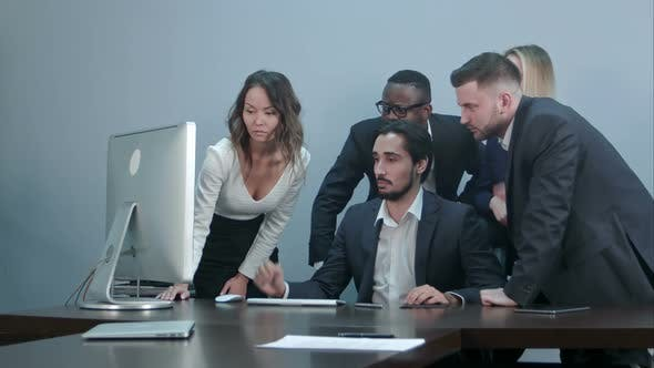 Cover Image for Group of Multiracial Business People Around the Conference Table Looking at Laptop Computer